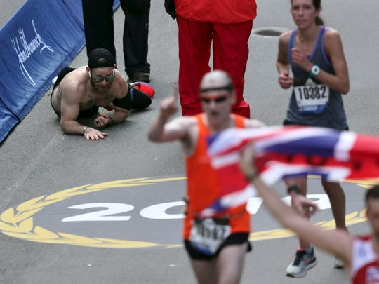 Micah Herndon, of Tallmadge, Ohio, crawls to the finish line in the 123rd Boston Marathon on Monday, April 15, 2019, in Boston.