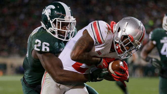 Ohio State running back Dontre Wilson, right, defended by Michigan State safety RJ Williamson scores on a seven-yard reception in East Lansing on Nov. 8, 2014.