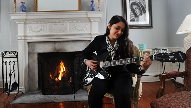 Angelica Garcia plays her guitar at her home, the St. James Episcopal Church Rectory in Accomac, Va., on Feb. 27. Garcia, a singer and songwriter, will be opening for recording artist Jeff Black on Friday, March 6, at St. James Church. The concert will raise money for the church's food pantry.