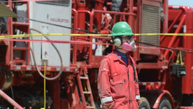 A worker walks by a pump at a fracking station near Dacono in this 2014 file photo. The Colorado Court of Appeals has asked to bow out of lawsuits filed against fracking restrictions passed in Longmont and Fort Collins.