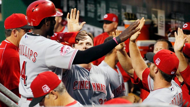 Reds second baseman Brandon Phillips (4) celebrates with the dugout after scoring a run against the Pittsburgh Pirates during the fourth inning Wednesday at PNC Park.