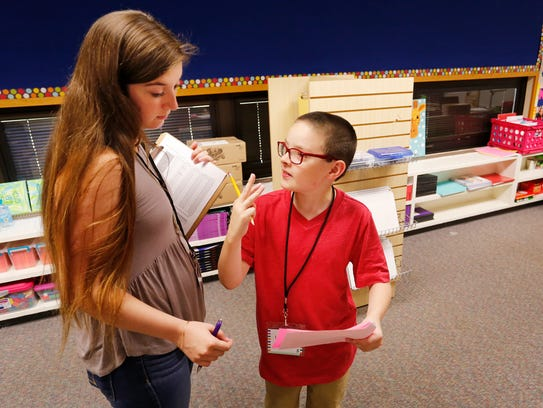 Third grade student Keyan McClellan is helped with