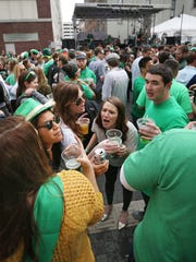 Revelers enjoy the warm weather at the Blarney Bash on Georgia Street in downtown Indianapolis on Saturday, March 14, 2015. The free outdoor festival featured live music, green beer and lots of food.
