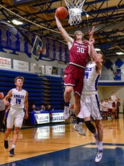 Milford's Gunnar Gustafson goes in for the dunk over