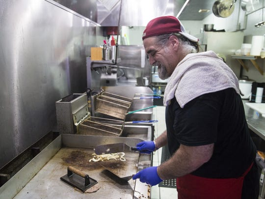 Rafel Diaz, one of the founders of Chi Chi's Cafe, prepares busted encebollao, a Cuban marinated steak.