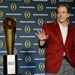 In this Jan. 12, 2016, file photo, Alabama head coach Nick Saban poses with the championship trophy during a news conference for the NCAA college football playoff championship in Scottsdale, Ariz.  Saban is one national title away from matching Bear Bryant's record and, with his 65th birthday coming up on Halloween, shows no signs of slowing down.