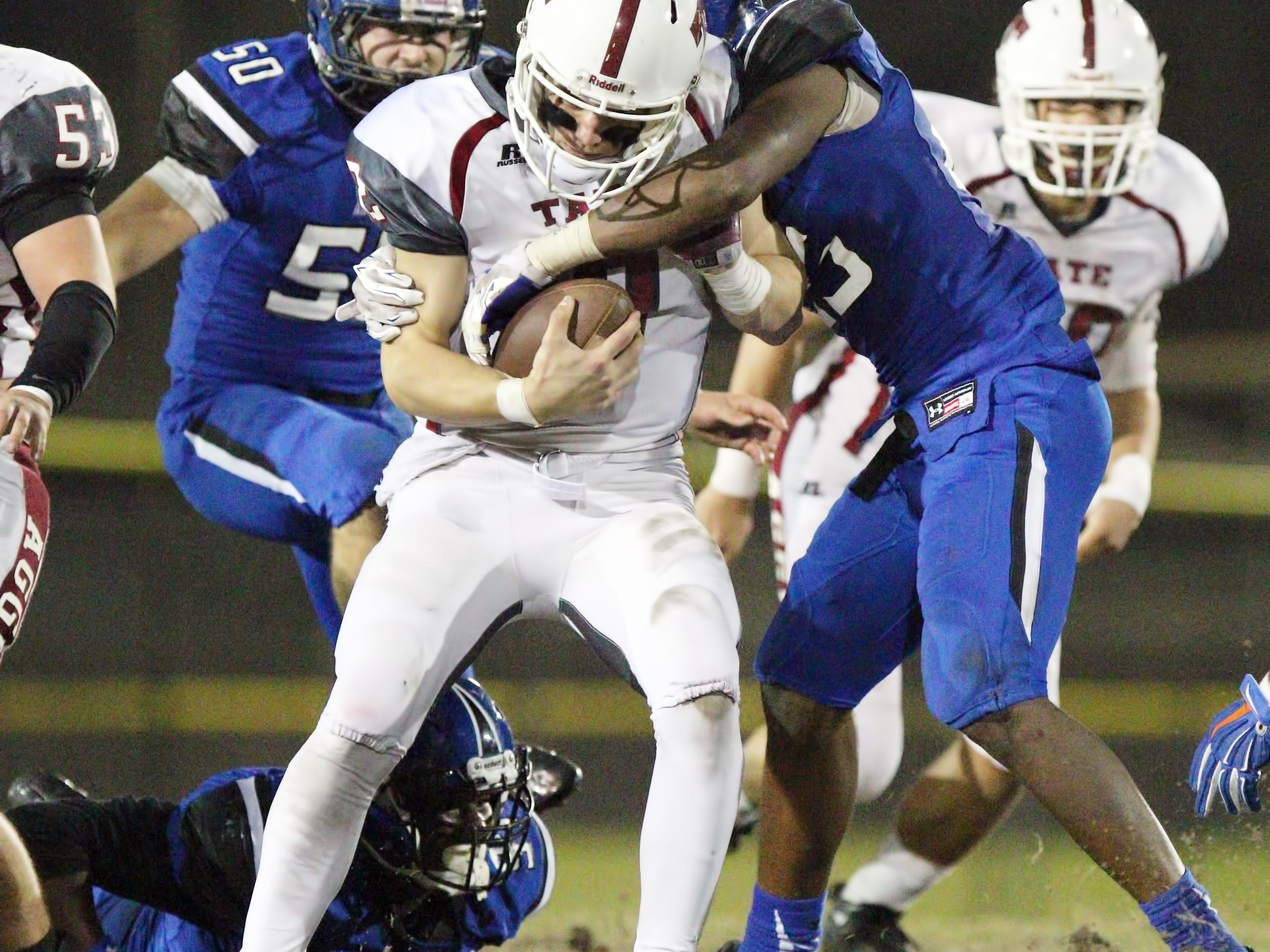 SEFFNER, FL. 12/4/2015 -- Armwood Hawks linebacker C.J. Jones pulls down Tate quarterback Sawyer Smith for a sack during the second half of Friday's Class 6A state semifinals game at Lyle Flagg Field. The Hawks went on to defeat the Aggies 53-19 to advance to the stat title game Saturday in Orlando. Photo by BILL WARD/PNJ