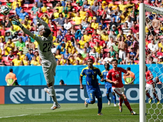 Ecuador's goalkeeper Alexander Dominguez leaps out to make a save in front of his goal during the group E World Cup soccer match between Switzerland and Ecuador at the Estadio Nacional in Brasilia, Brazil, Sunday, June 15, 2014. At right, Ecuador's Jorge Guagua and Switzerland's Valentin Stocker.  (AP Photo/Marcio Jose Sanchez)