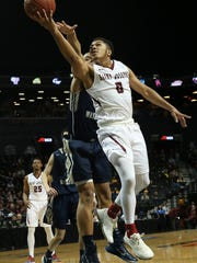 Saint Joseph guard Lamarr Kimble (0) goes to the basket past George Washington forward Kevin Larsen during the first half of an NCAA college basketball game in the Atlantic 10 men's tournament, Friday, March 11, 2016, at New York. (AP Photo/Mary Altaffer)