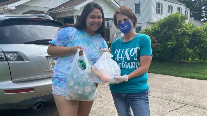 Upward Bound student Jael Salceda (left) receives a sack lunch from SSC Upward Bound Coordinator Amber Cooper.