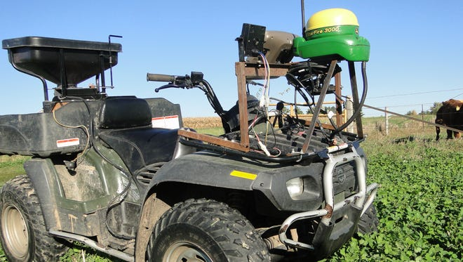Jeff Gaska uses an ATV equipped with RTK guidance technology to guide his establishment of clover in a wheat field in spring.