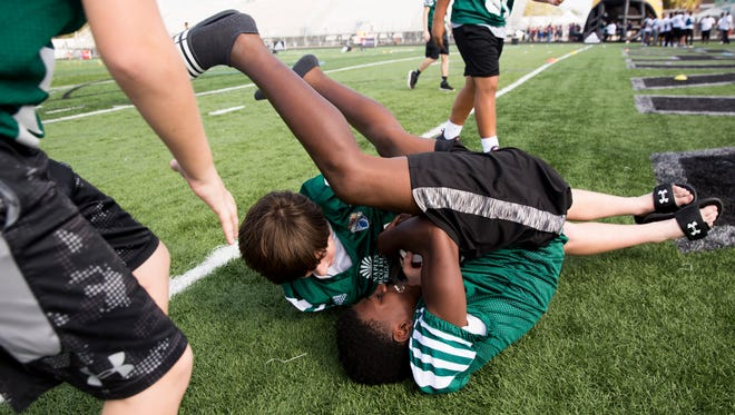 James Johnson, 12, does a somersault while wrestling for the ball with Dane Aaberg, 12, both with the 6th Grade team from Dallas, Texas as middle-school football players from across the country showed up for registration and a pep rally to kick off the FBU National Championships at Gulf Coast High School Sunday, Dec. 17, 2017 in Naples.