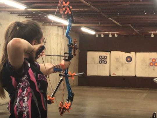 Central High School's Cie Rangel lines up a shot during archery practice in the basement archery range at The Outdoorsman.