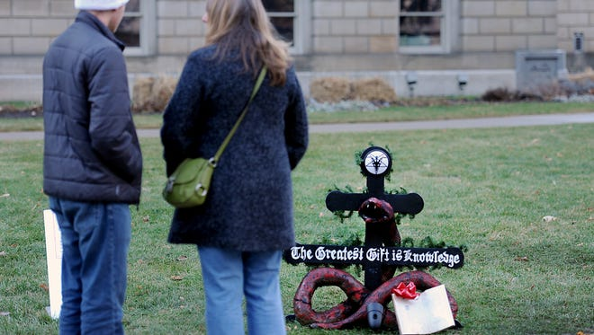 """People visit the  """"Snaketivity"""" scene in downtown Lansing Tuesday 12/23/2014 put up by the Satanic Temple of Detroit  on the grounds of the State Capitol.  The grounds at the Capitol are also hosting a small Nativity scene  .  Both displays must be taken down at night and put up in the morning."""