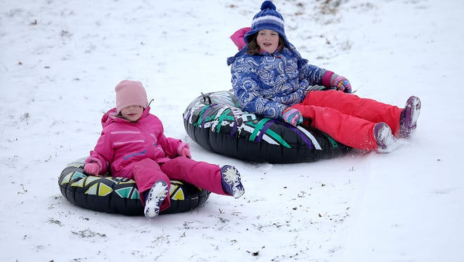 Norah Styers-Barnett,left,  and sister Gillian take advantage of the new snow to do a little sledding Tuesday, January 6, 2015, afternoon at Garfield Park.