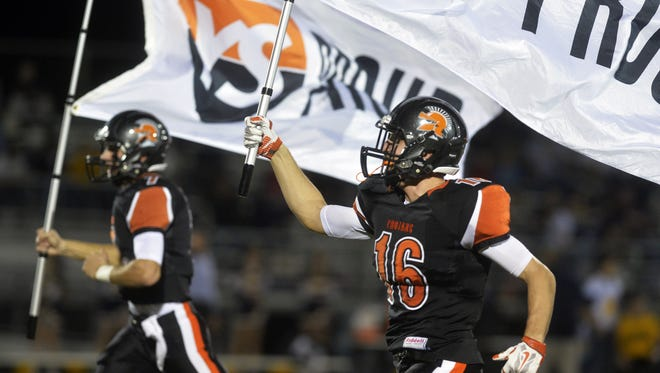York Suburban's Thomas Merkle, left, and Brad Smith carry flags onto the field before their regular-season finale at home against Eastern York on Nov. 6. York Suburban won 30-7, marking the team's eighth-straight win. The Trojans hold an 8-2 record entering this week's District 3 Class AA tournament.