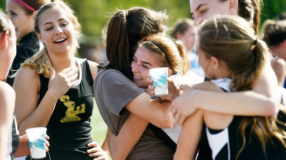 Delone Catholic girls greet each other after placing second in the 3200-meter relay during the YAIAA Track and Field Championships Friday, May 13, 2015, at Dallastown.