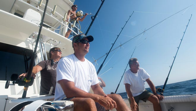 """""""If you go into this to win, and expect to win, you better not fish. It's got to be for the love of the sport,"""" said John Kunzler, right, owner of the boat """"Chasin Tails."""" Kunzler, along with, from foreground clockwise: Mike Waldhauser, Buddy Trala and Andrew Dietz were part of the crew on Kunzler's boat hoping to win big money during the White Marlin Open in Ocean City, Maryland."""