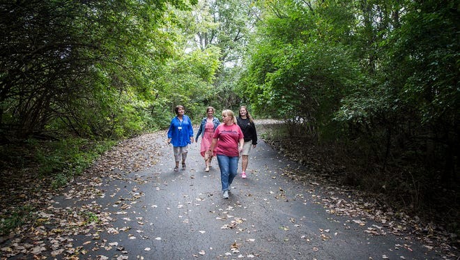 The Youth Opportunity Center's walking club walks a trail on a back lot at the facility Wednesday afternoon.  The club meets Mondays and Wednesdays each week.