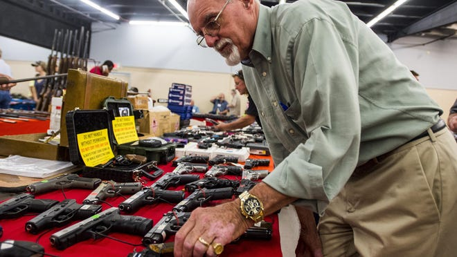 Larry DuBose looks through a selection of handguns in a booth during the Louisiana Gun & Knife Show at the Lafayette Event Center in Lafayette, Saturday, Aug. 8, 2015.