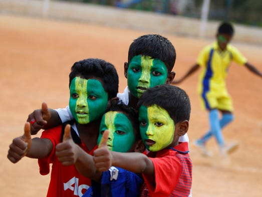 FACT: According to wallethub.com, Brazil is the only nation to have appeared in all 20 World Cups.<br /> Here, Indian boys with faces painted in colors resembling those of the Brazil's flag pose for photographer in Bangalore, India. Soccer fans around the world are gearing up to watch the World Cup soccer tournament that kicks off Thursday in Brazil.