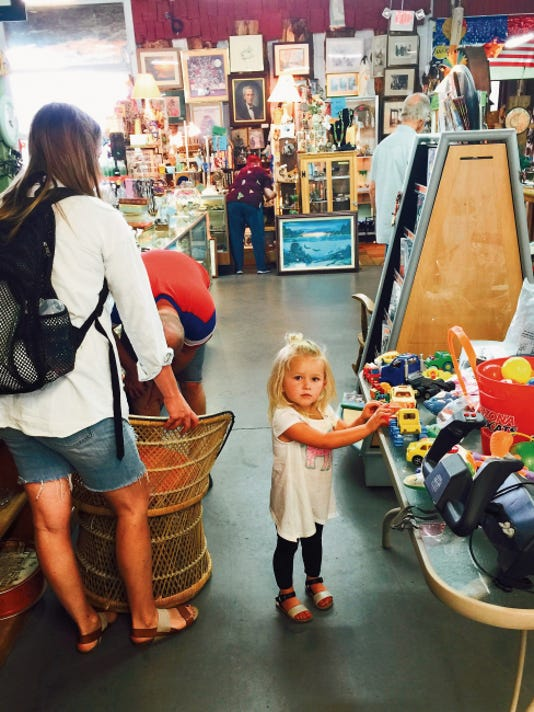 A little collector examines treasures of her own as her parents shop.