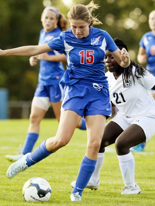 Spring Grove's Lucy Wierman (15) prepares to pass against Dallastown's Jordan Lese during the second half of Thursday's soccer match at Dallastown. Dallastown won, 5-0.