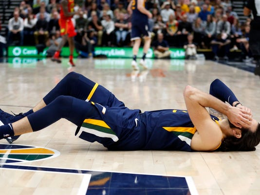 Utah Jazz guard Ricky Rubio falls to the court after a foul from Atlanta Hawks guard Dennis Schroeder during the second half of an NBA basketball game Tuesday, March 20, 2018, in Salt Lake City. (AP Photo/Rick Bowmer)