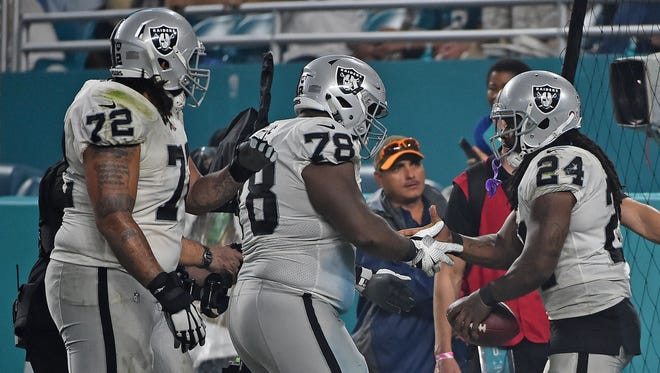 Oakland Raiders running back Marshawn Lynch (24) celebrates with teammates after his touchdown against the Miami Dolphins during the second half at Hard Rock Stadium.