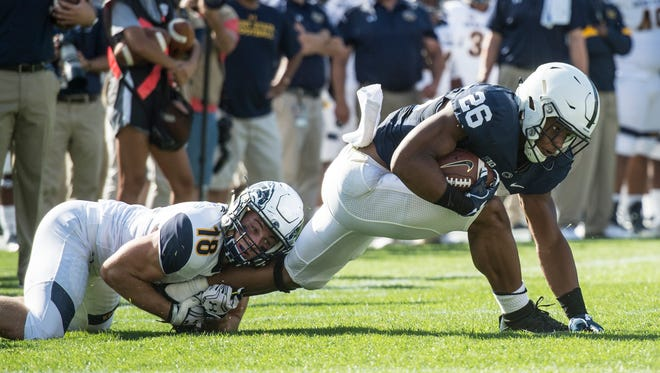 Penn State Nittany Lions running back Saquon Barkley (26) tries to breaks away from Kent State Golden Flashes safety Nate Holley (18) during the Penn State season opener against Kent State on Saturday at Beaver Stadium.