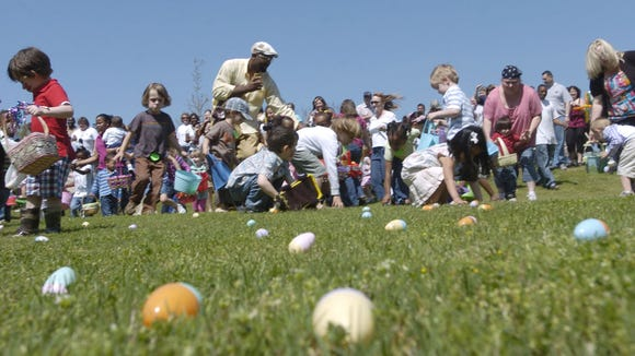 Children gather eggs Saturday during the annual Easter
