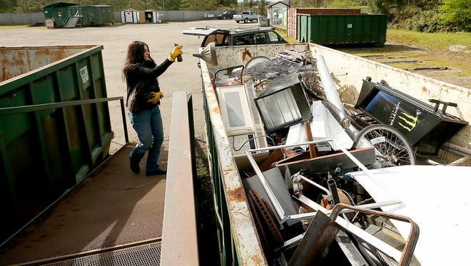 Michelle Kelly, of Poulsbo, tosses scrap metal into a bin at the Poulsbo Recycle Center.