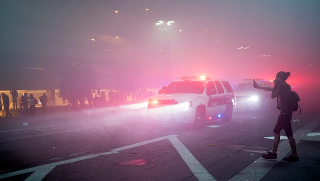 Protesters cover their faces from a cloud of gas fired by police outside the Phoenix Convention Center following President Trump's speech on Aug. 22, 2017.