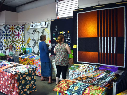 Visitors admire quilts on the wall of ThreadBear's