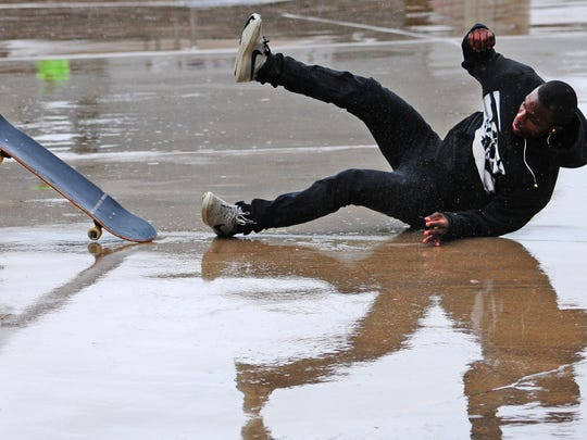 Ricco Porter of Green Bay hits the wet pavement while trying to stick a landing during the 5th annual Going Big in the Bay skateboard competition and fundraiser at Joannes Sk8 Park in Green Bay on Saturday, October 4, 2014.