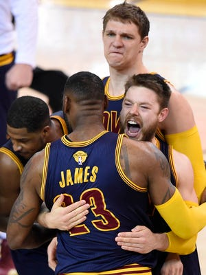 Cleveland Cavaliers forward LeBron James (23) celebrates with guard Matthew Dellavedova (8) the 95-93 victory against the Golden State Warriors in game two of the NBA Finals at Oracle Arena.