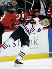 New Jersey Devils left wing Taylor Hall, left, hits Chicago Blackhawks defenseman Gustav Forsling (42), of Sweden, during the second period of an NHL hockey game, Saturday, Dec. 23, 2017, in Newark, N.J.