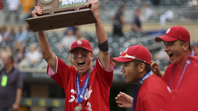 Henry Sibley's Dillon Orth holds up the trophy at the end of the awards ceremony after the team defeated Mahtomedi 8-4 in the state Class 3A baseball championship game Monday, June 20, 2016, in Minneapolis. (Jeff Wheeler/Star Tribune via AP)