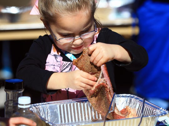 Alexa Garrett, 5, prepares a round steak as she competes in the Kids' BBQ Cookoff during the 81st Annual Nueces County Junior Livestock Show Saturday, Jan. 9, 2016, at the Richard M. Borchard Regional Fairgrounds in Robstown.