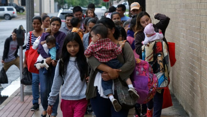 A group of migrants released from federal custody on June 20, 2018, walk down the street toward a bus station in McAllen, Texas. Adults are wearing GPS ankle monitors as a condition of their release, and have been scheduled for hearings before a judge.