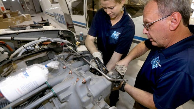 Doris Gossett, an aircraft mechanic, left, and Matt Taylor, aircraft maintenance manager, right, work together to remove a cylinder from a Piper Seminole at the Murfreesboro Municipal Airport. Gossett and Taylor work for MTSU's School of Aerospcace Flight School.