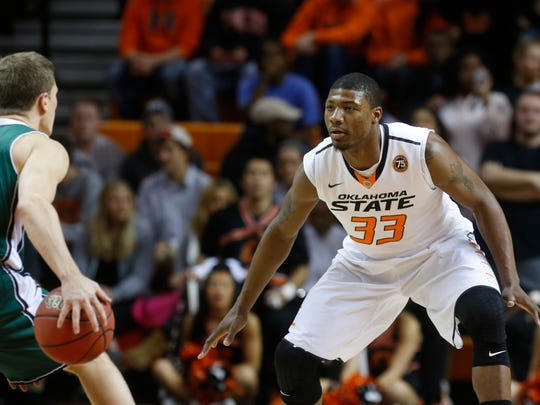 Oklahoma State guard Marcus Smart (33) defends Utah Valley guard Holton Hunsaker (12) in the first half of NCAA college basketball game in Stillwater, Okla., Tuesday, Nov. 12, 2013.