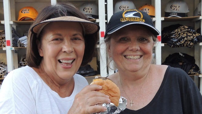 Colt 45s volunteer Terri Stratte enjoys a burger with a friend at Tiger Field.