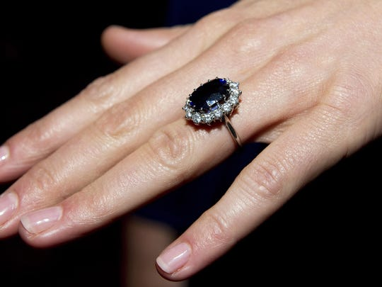 Princess Diana's sapphire engagement ring on the left