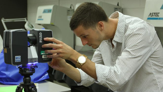 FGCU graduate student Shawn Dahl works with a Faro Laser Scanner during class on Tuesday.