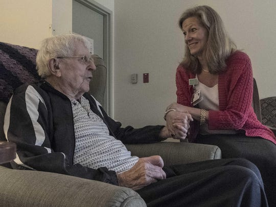 Anna-Gene O'Neal holds hands with Jim Regan, a patient