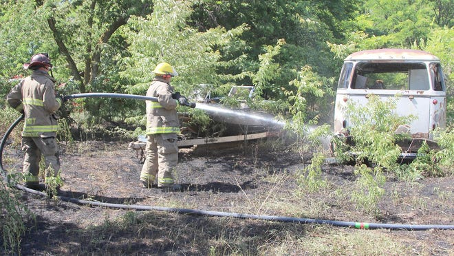 Pratt Fire Lt. Chad Van Slyke (left) helps Firefighter Mac Callaway as he sprays hot spots beneath an old vehicle at a grass fire at 1102 North Thompson on June 5. A shed and dog house burned in the fire.