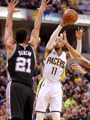 Indiana Pacers guard Monta Ellis (11) passes the basketball defended by San Antonio Spurs forward Tim Duncan (21) in the first half of an NBA basketball game, Monday, March 7, 2016, in Indianapolis. Indiana won 99-91. (AP Photo/R Brent Smith)