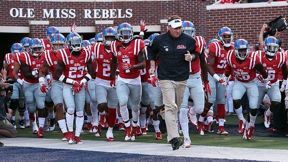 Coach Hugh Freeze leads his team onto the field before a game against Vanderbilt last season.