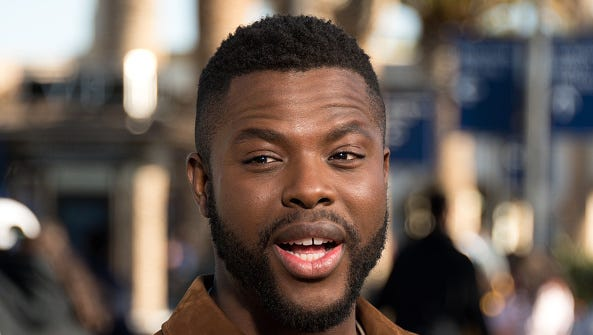"""Winston Duke takes a selfie with fans at """"Extra"""" at Universal Studios Hollywood on February 19, 2018 in Universal City, California."""